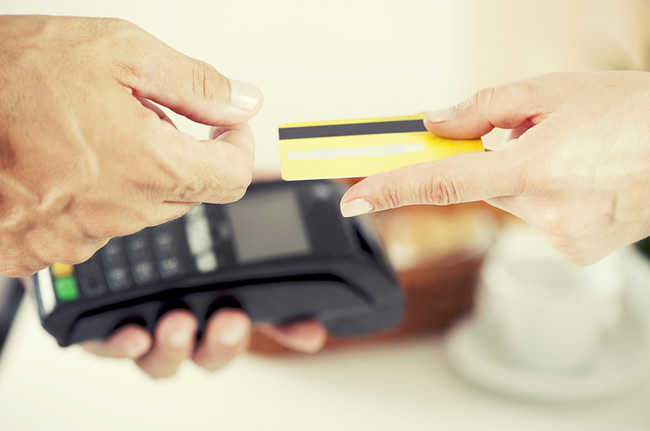 credit card being swiped through a terminal